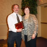 Image of Pat Miller accepting award for Father Charles Miller